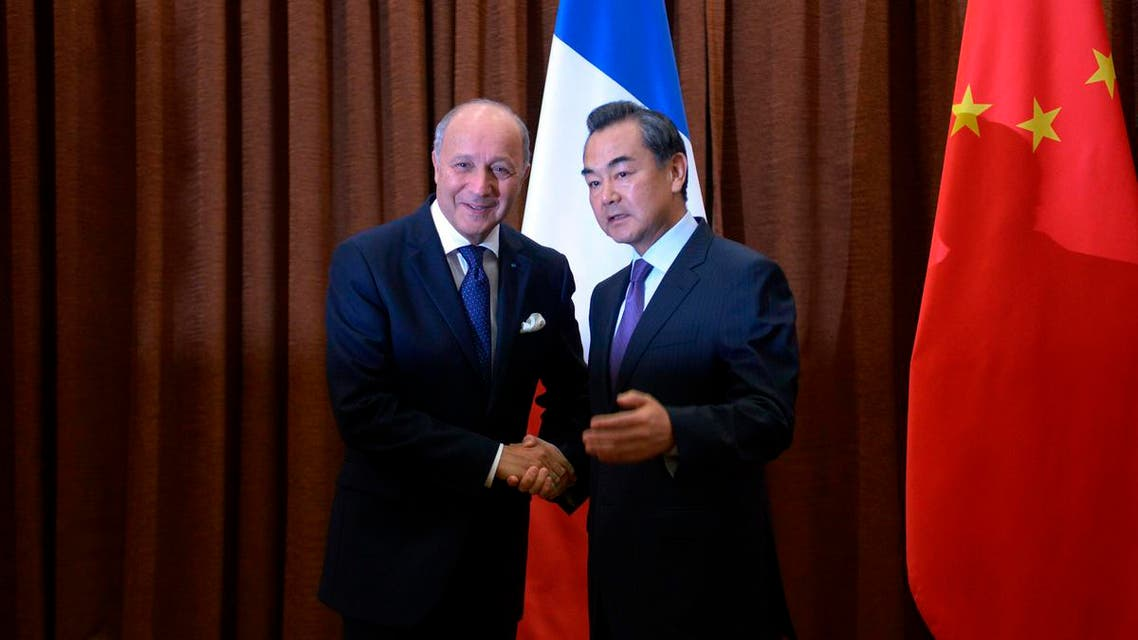 French Foreign Minister Laurent Fabius (L) shakes hands with Chinese Foreign Minister Wang Yi before their meeting at the Chinese Foreign Ministry in Beijing, September 15, 2013. (Reuters)