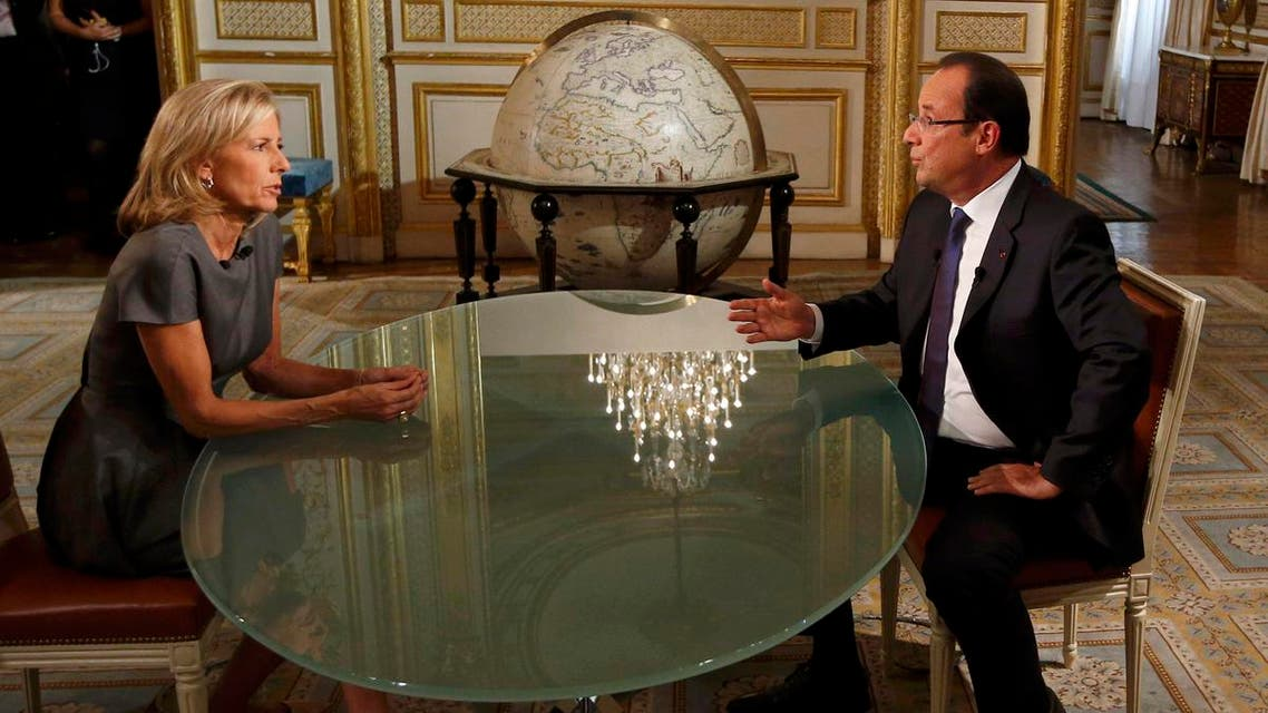 France's President Francois Hollande (R) takes part in a televised interview with French journalist Claire Chazal on French TF1 television channel's prime-time evening news broadcast in Paris, September 15, 2013. reuters