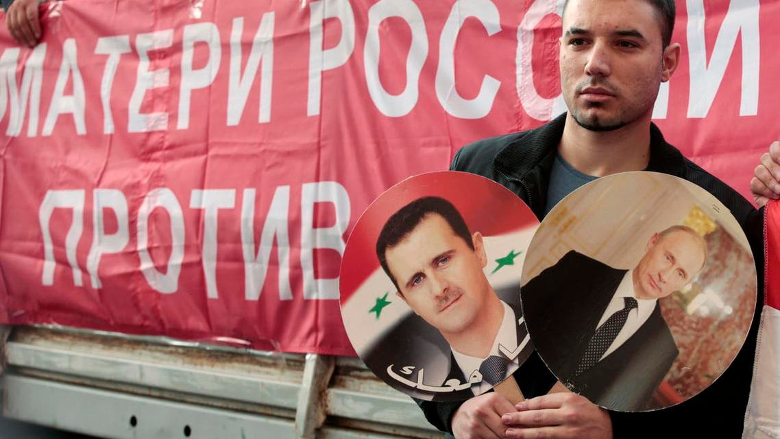 A participant hold images of Russian President Vladimir Putin and Syrian President Bashar al-Assad during an anti-war protest organised by the Communist party near the U.S. embassy in Moscow September 12, 2013. (Reuters)