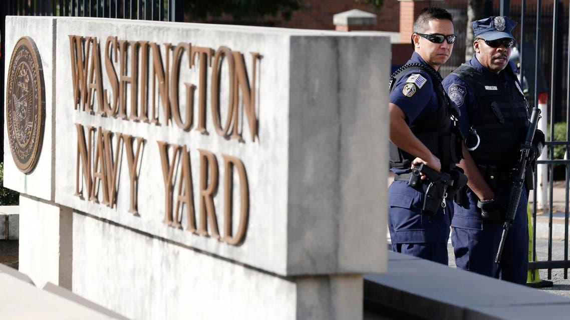 A Washington, DC Metropolitan police officer (L) and a Naval District Washington policemen (R) stand guard at the main gate of the Washington Navy Yard in Washington, September 17, 2013. reu