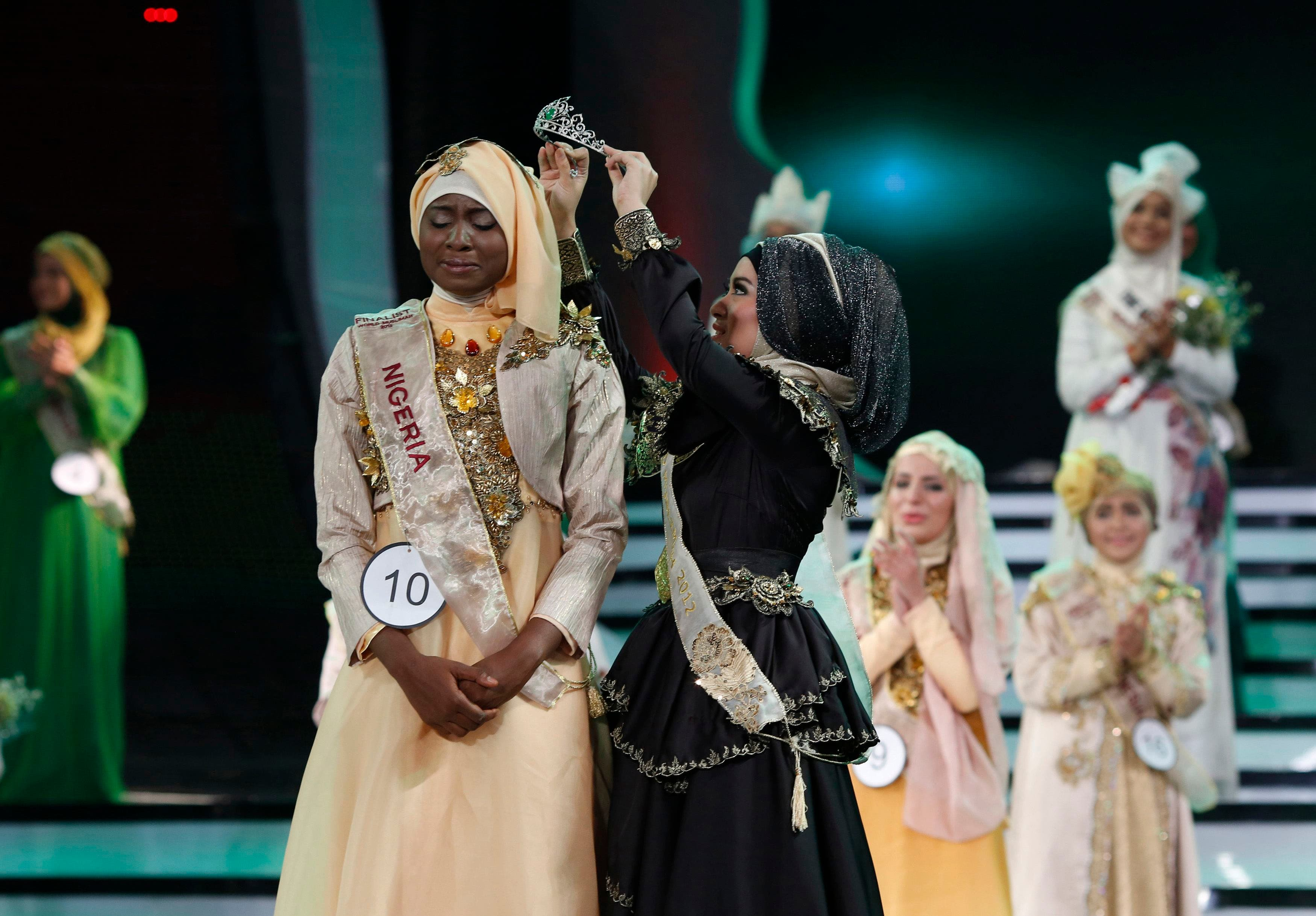 Nigerian Obabiyi Aishah Ajibola is crowned by her predecessor World Muslimah 2012 Nina Septiani of Indonesia (R) after being named World Muslimah 2013 during the third Annual Award of World Muslimah in Jakarta Sept. 18, 2013. (Reuters)