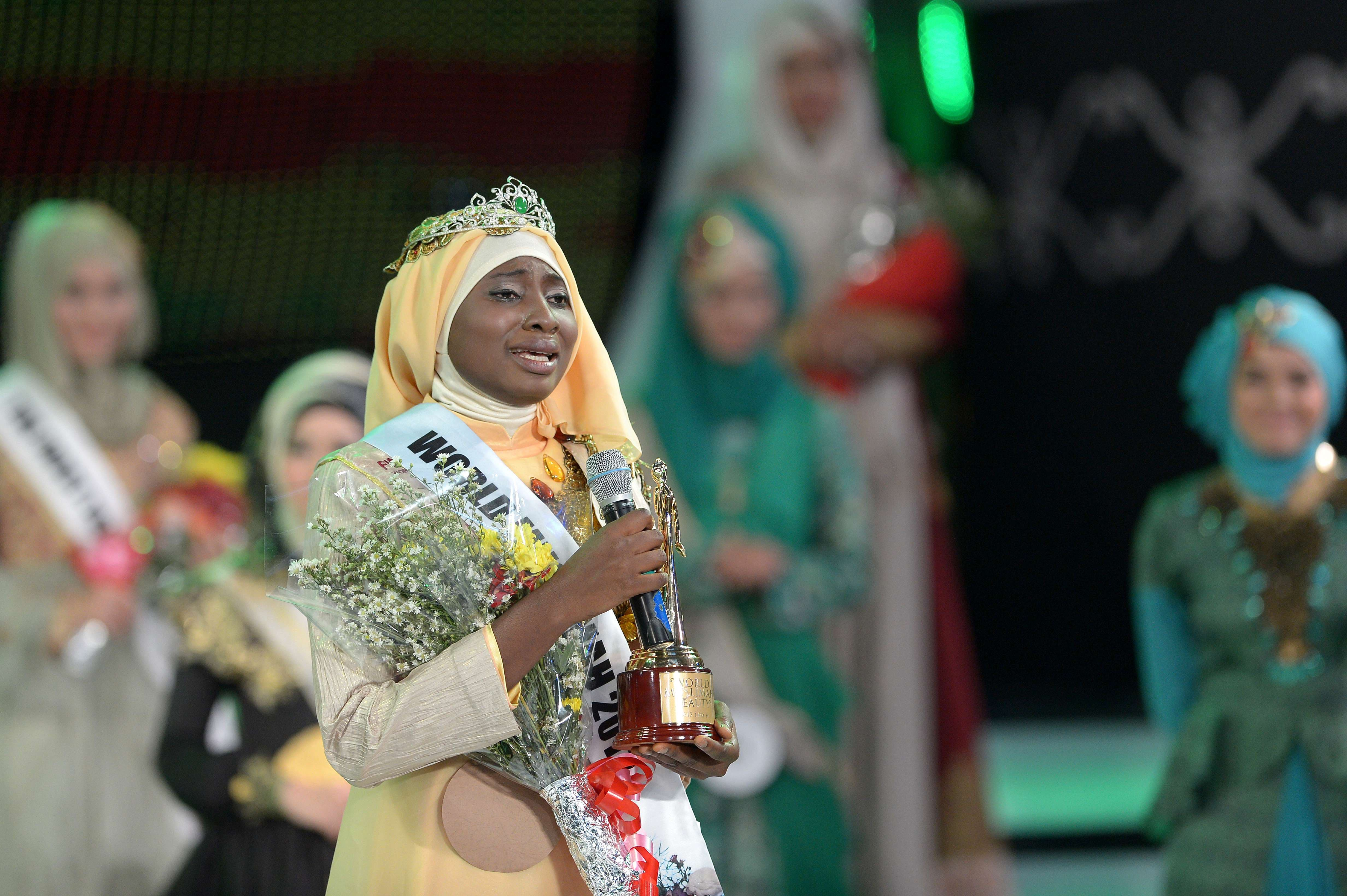 Contestant of the Muslimah World Obabiyi Aishah Ajibola (L) of Nigeria is crowned by Indonesian Muslimah 2012 during the Muslimah World competition in Jakarta on Sept.18, 2013.  (AFP)