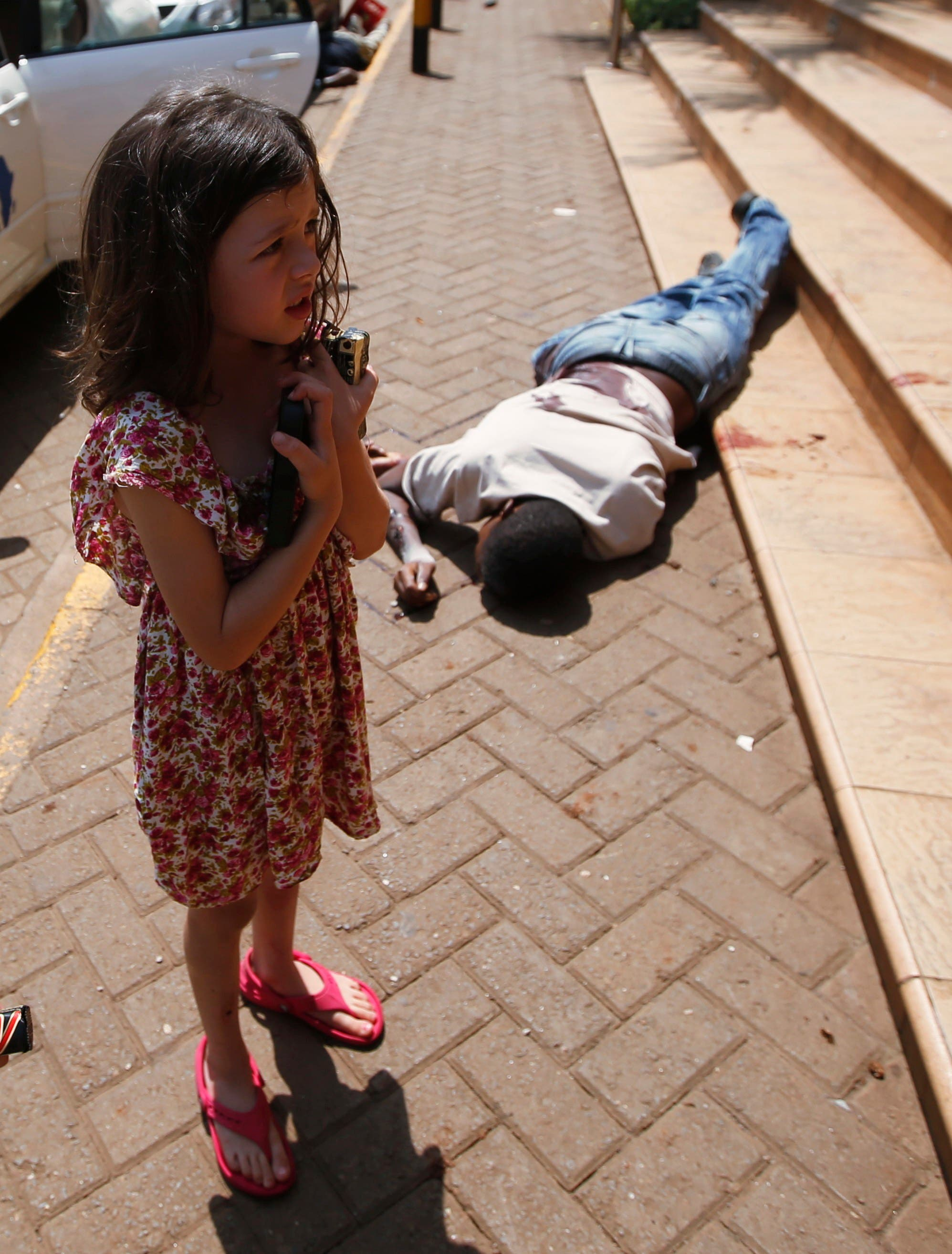 A girl stands by the body of a man after escaping Westgate Shopping Centre in Nairobi. (Reuters)