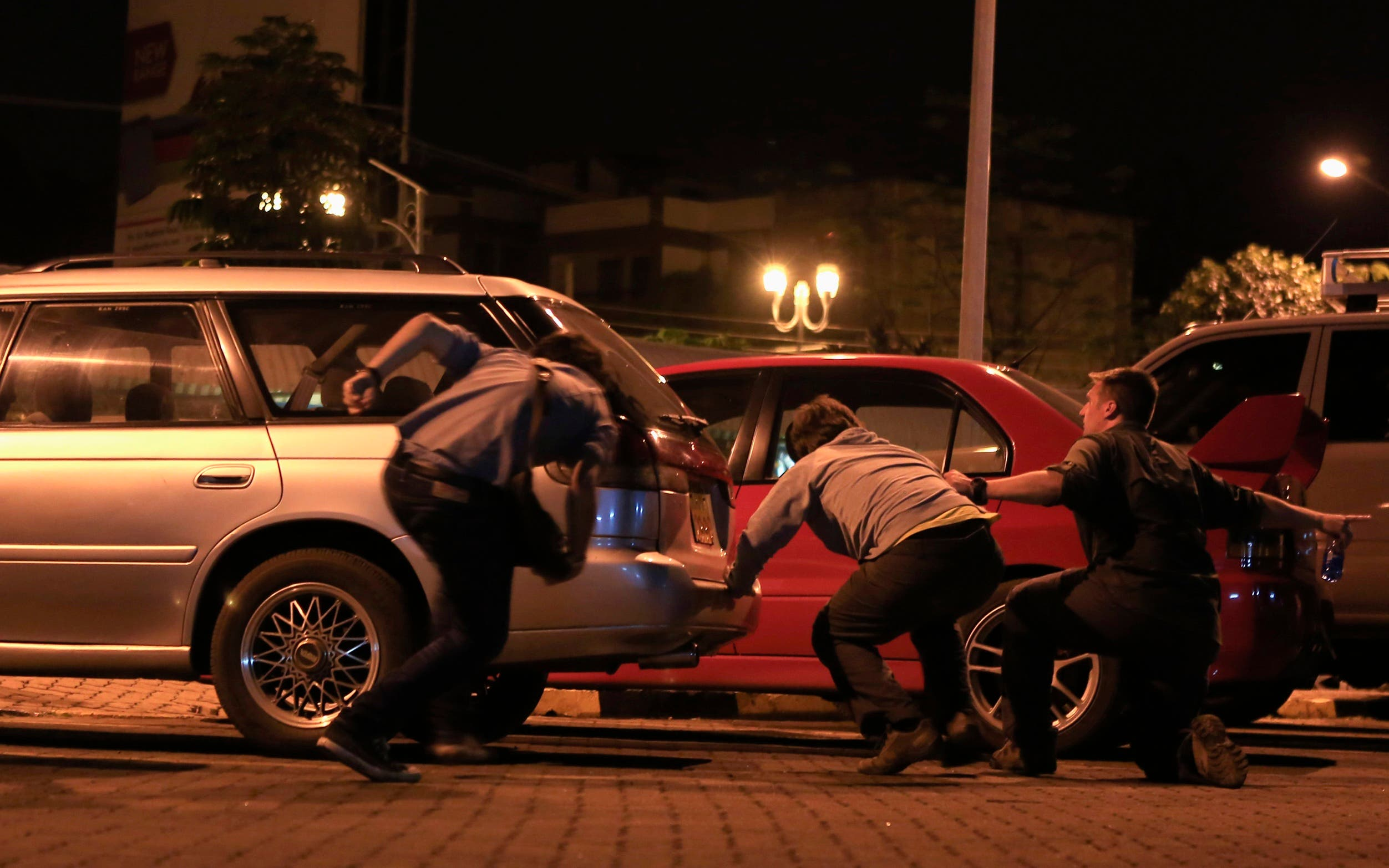 People run for cover as the stand-off continues into the night at Westgate Shopping Centre in Nairobi. (Reuters)