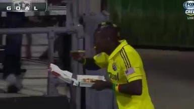 """لاعب غاني يحتفل بهدفه بتناول قطعة من """"البيتزا"""""""