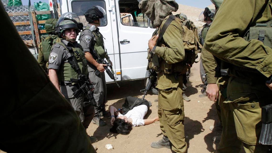 French diplomat Marion Castaing lays on the ground after Israeli soldiers carried her out of her truck containing emergency aid, in the West Bank herding community of Khirbet al-Makhul, in the Jordan Valley September 20, 2013. reu