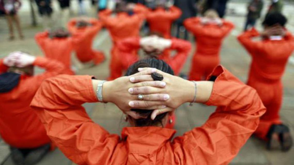 Activists from Amnesty International dressed as Guantanamo Bay detainees take part in a photo call in front of the Waterfront Hall in Belfast June 16, 2013,  rey