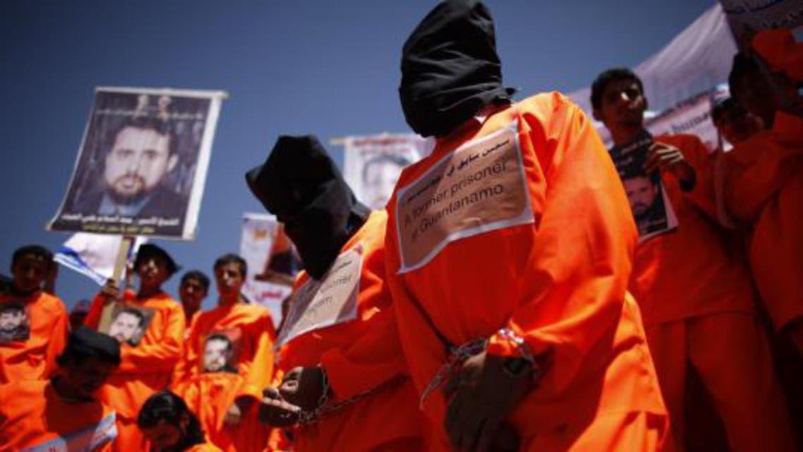 Former Guantanamo Bay detainees Walid al-Qadasi (R) and Sadiq Muhammad Saeed wear black hoods during a protest to demand the release of Yemeni detainees from Guantanamo Bay, outside the U.S. embassy in Sanaa April 16, 2013. reu