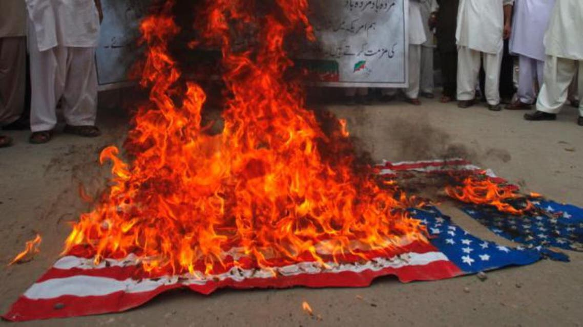 "Protesters burn an American flag following to release of the controversial short film ""Innocence of Muslims"" in Peshawar, Pakistan, September 2012. reu"