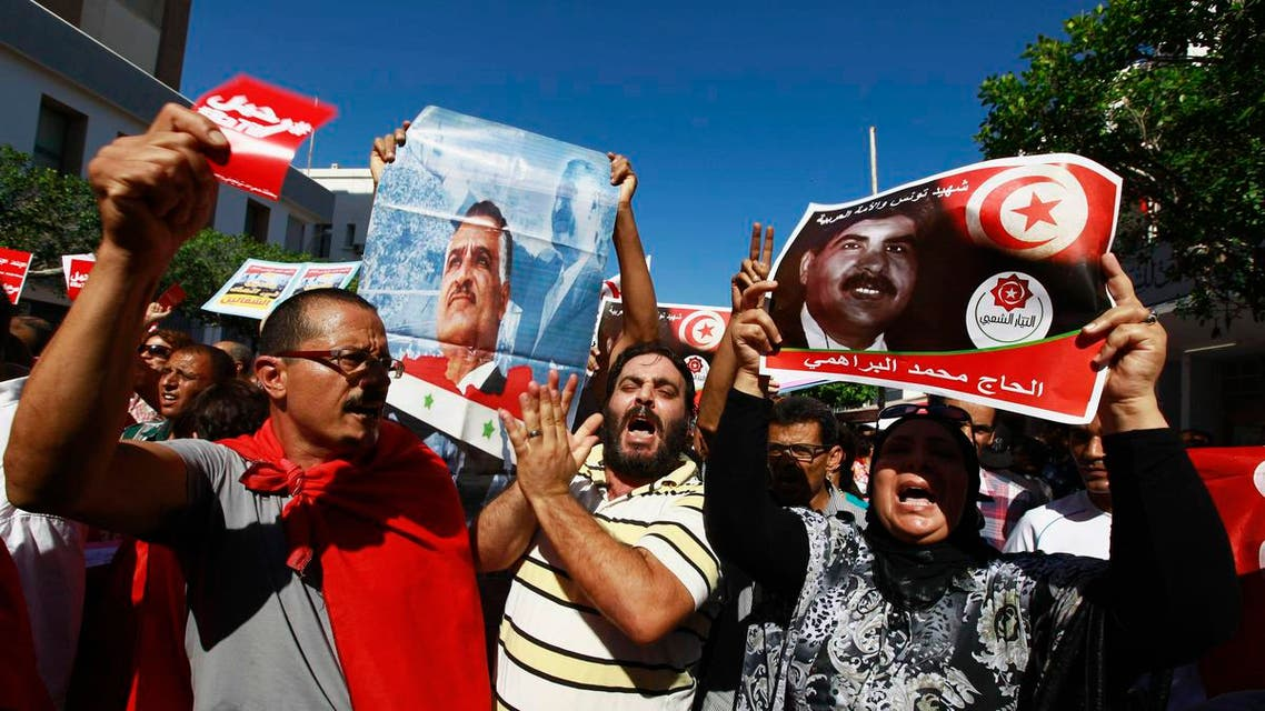 Protesters hold up and a picture of slain opposition leader Mohamed Brahmi during an anti-government demonstration rallying for the dissolution of the Islamist-led government in Sfax, 170 miles (270 km) southeast of Tunis September 26, 2013.