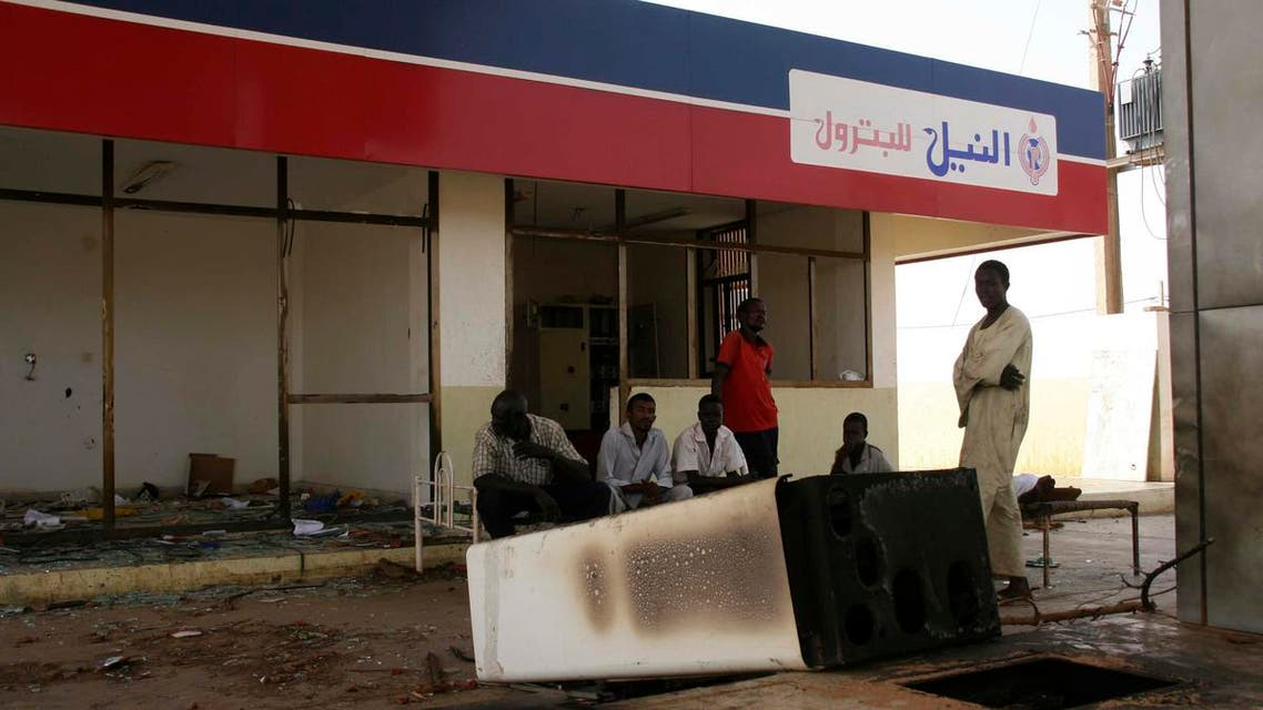 Workers wait at a burnt gas station during protests over fuel subsidy cuts in Khartoum September 26, 2013. (Reuters)