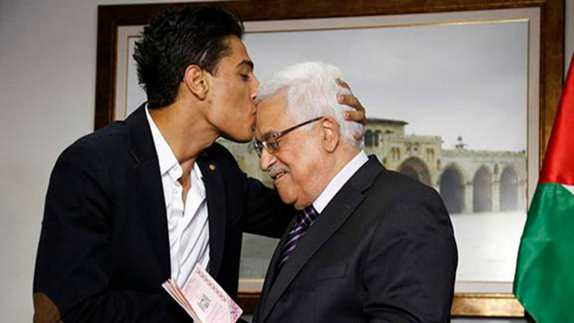 """Arab Idol"" Mohammed Assaf kisses Palestinian President Mahmoud Abbas as he hands him a diplomatic Palestinian Authority passport during their meeting in the West Bank city of Ramallah, July 1, 2013.   reu"