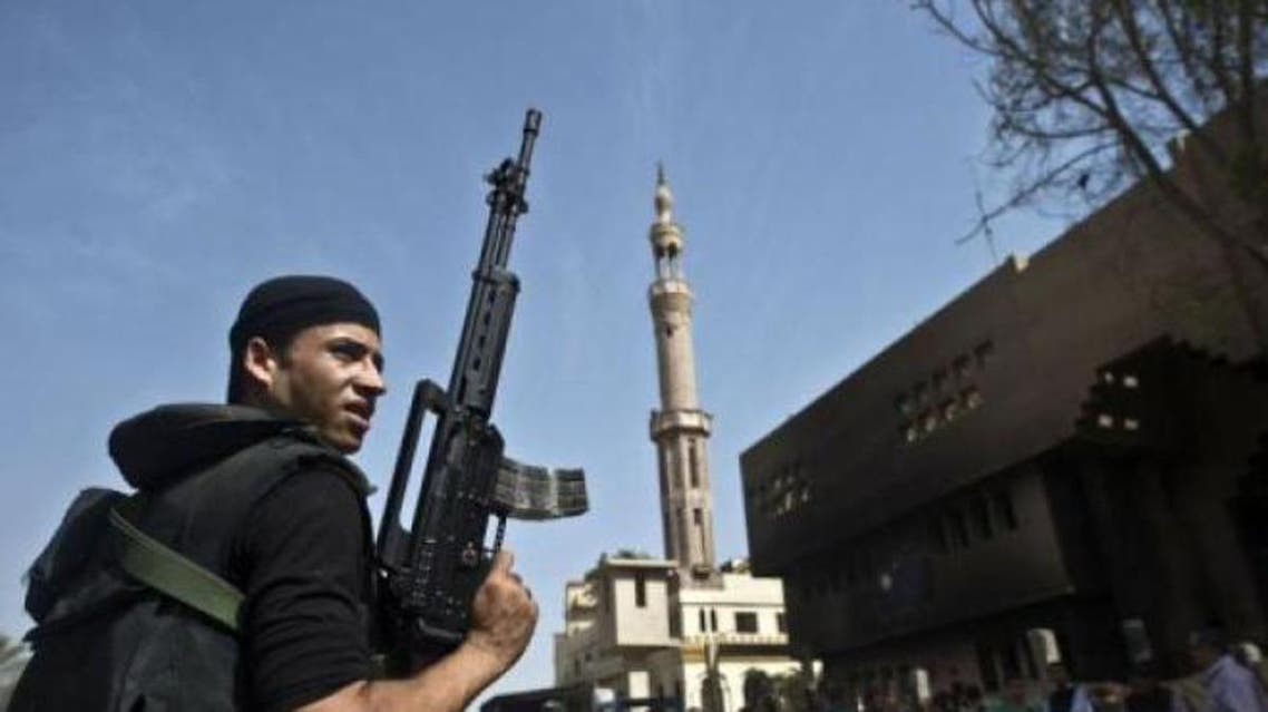 An Egyptian armed policeman stands in front of a burnt police station in the village of Kerdassah on the outskirts of Cairo, on September 19, 2013. (File photo: AFP)