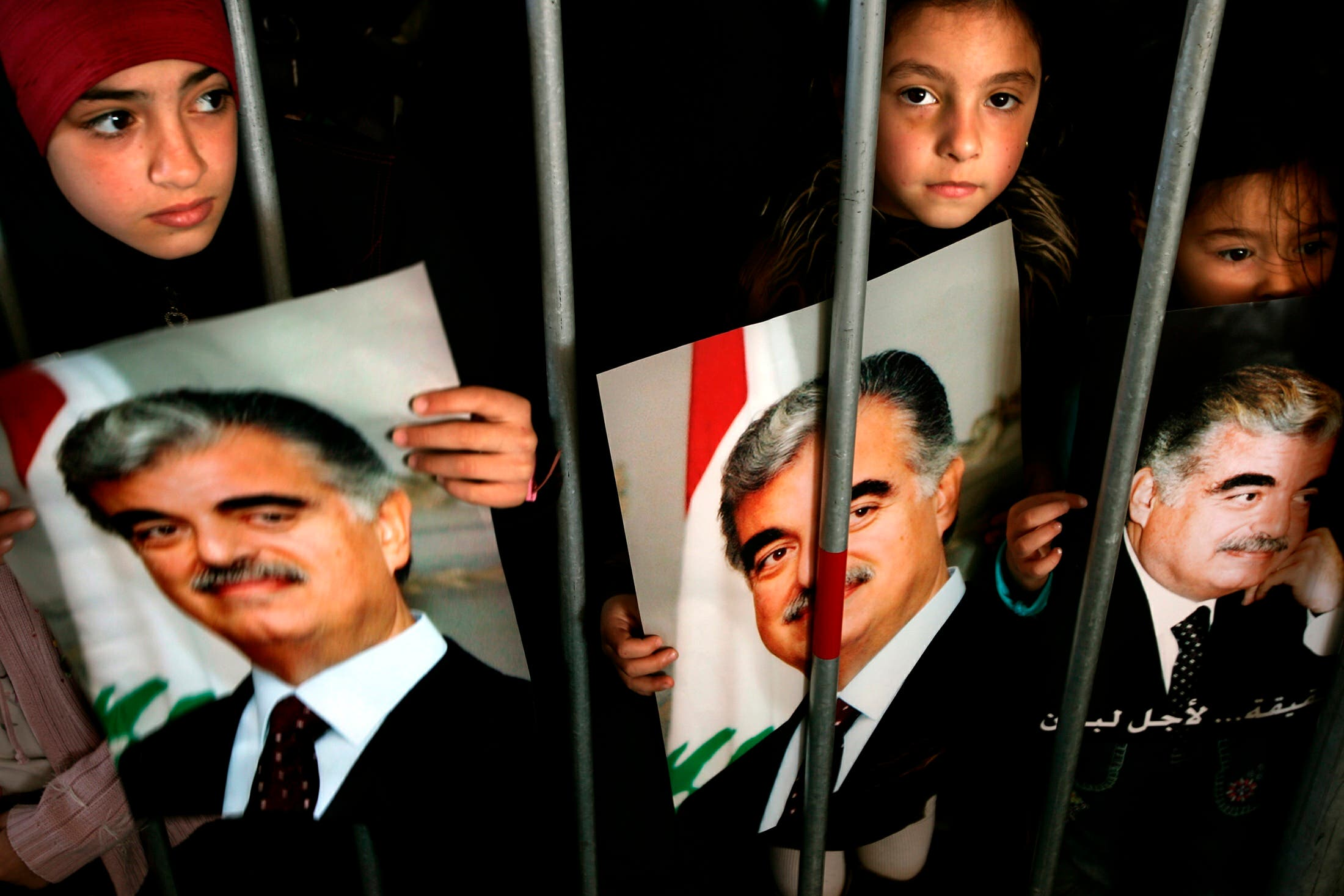 Lebanese Muslim girls hold pictures of former Prime Minister Rafik al-Hariri as they visit his grave in Beirut's Martyrs Square. (Reuters)