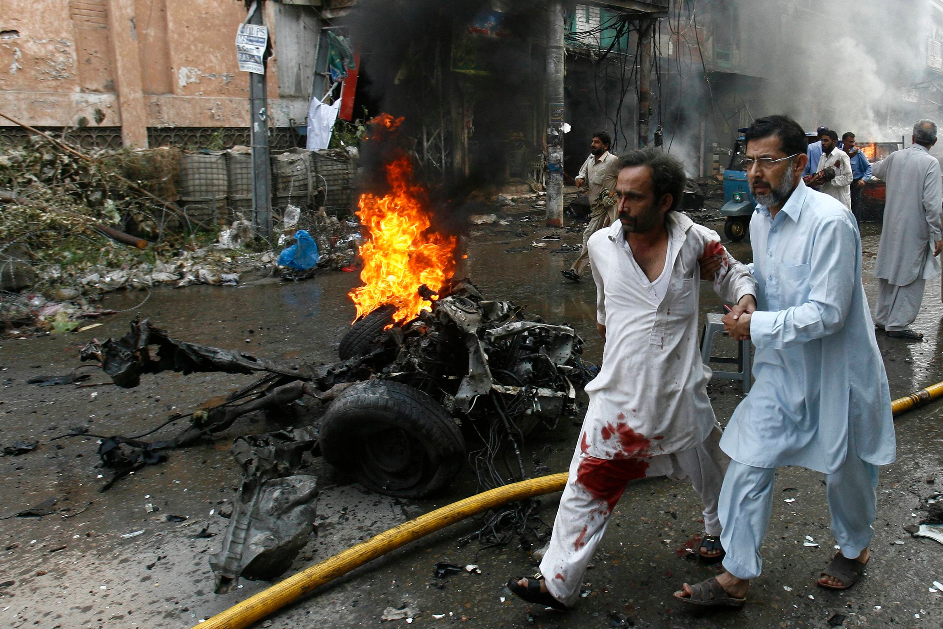 A man helps an injured man walk away from the site of a bomb attack in Peshawar, Pakistan on Sept. 29, 2013. (Reuters)