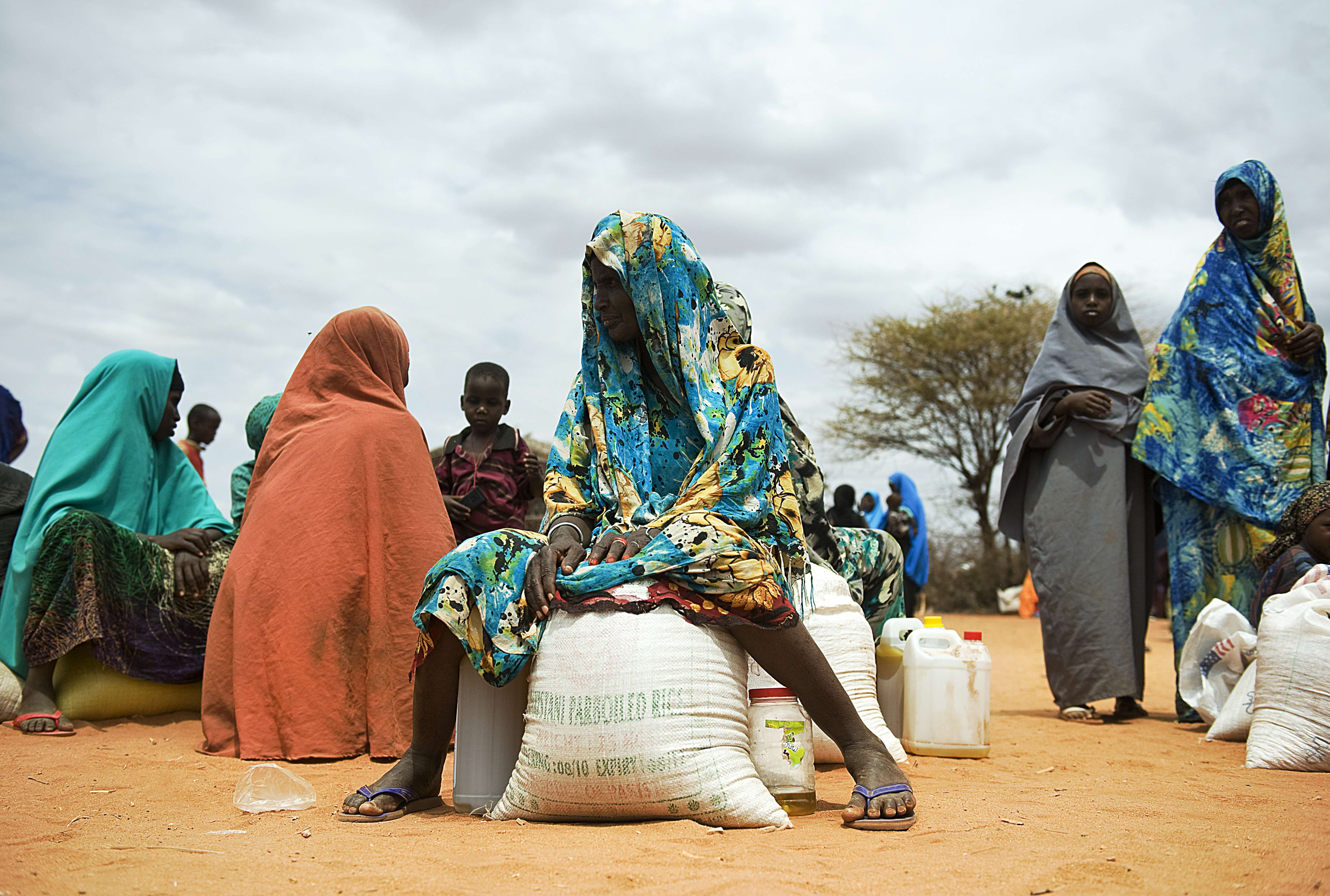 Somali women sitting with their rations after receiving relief food during a distribution excercise at an IDP camp in Dollow, northern Somalia. (AFP)