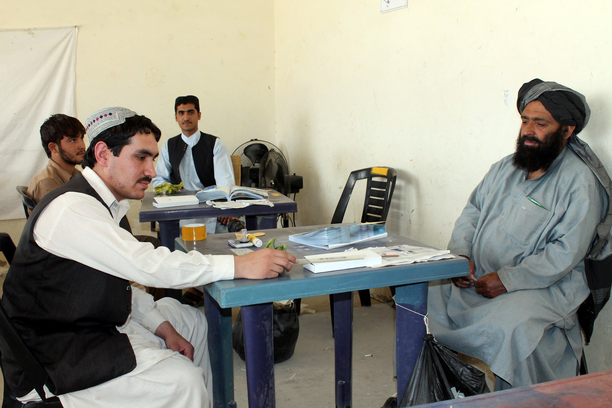 An Afghan man (R) waits to receive his identification card to vote in upcoming elections at a registration center in Kandahar on Sept. 28, 2013. (AFP)