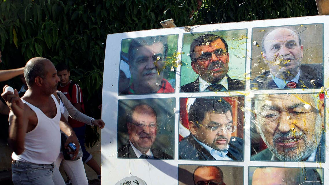 An anti-government protester throws an egg at a poster of Tunisian politicians, including