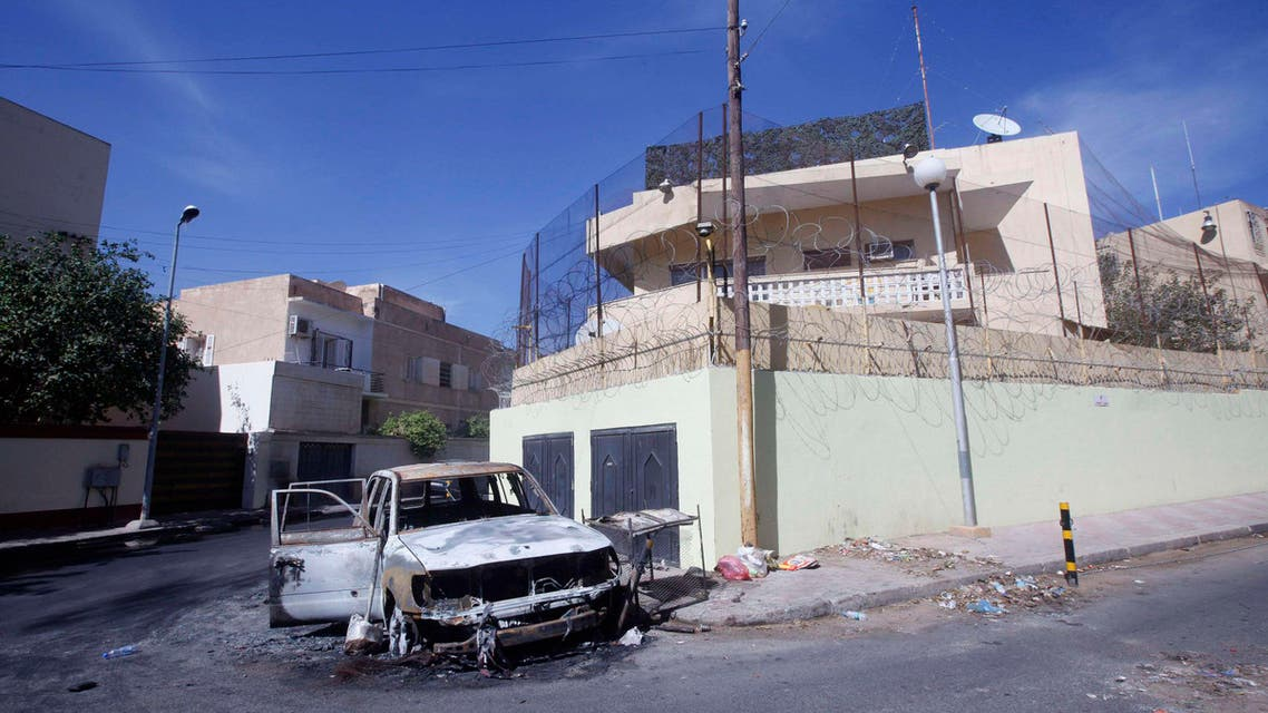 A damaged car is seen in front of the Russian embassy, a day after it came under attack in Tripoli October 3, 2013.