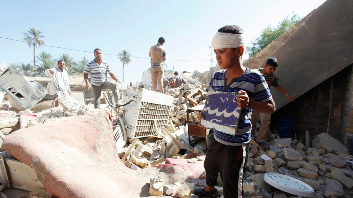 Civilians look at a damaged Shi'ite mosque a day after a suicide bomb attack in Mussayab, 60km (40 miles) south of the capital Baghdad, September 30, 2013.