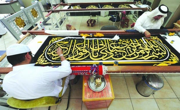 Saudi worker sew Islamic calligraphy in gold thread on a drape to cover the Kaaba at the Kiswa factory in the holy city of Mecca afp