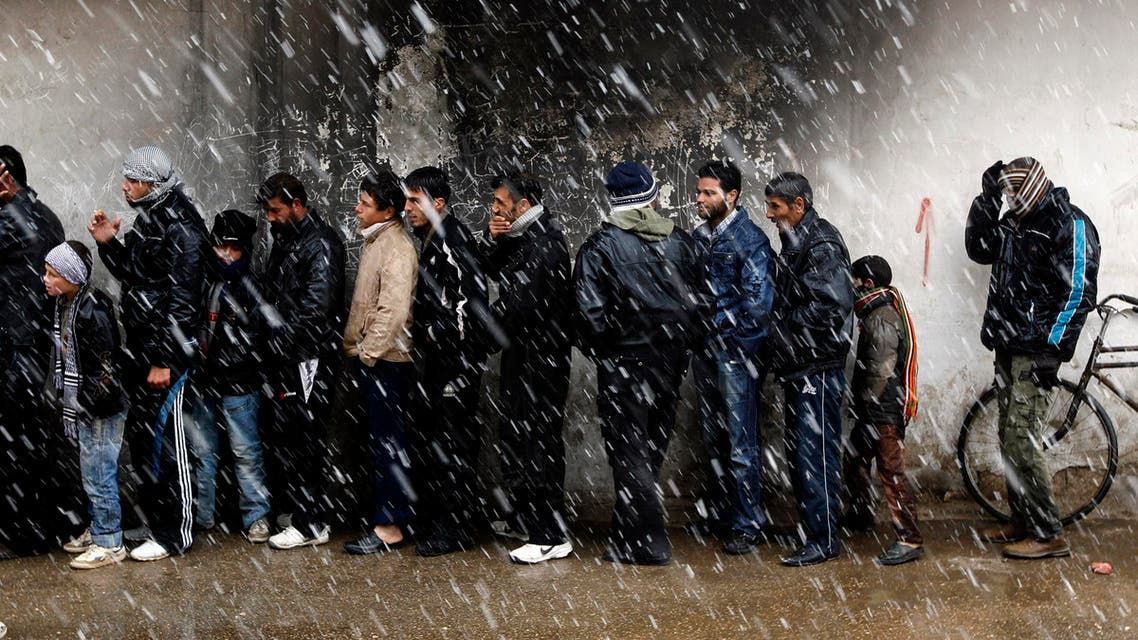 Men wait to buy bread in front of a bakery shop during winter in Al Qusayr, a city in western Syria about 4.8km (3 miles) southwest of Homs, March 1, 2012.