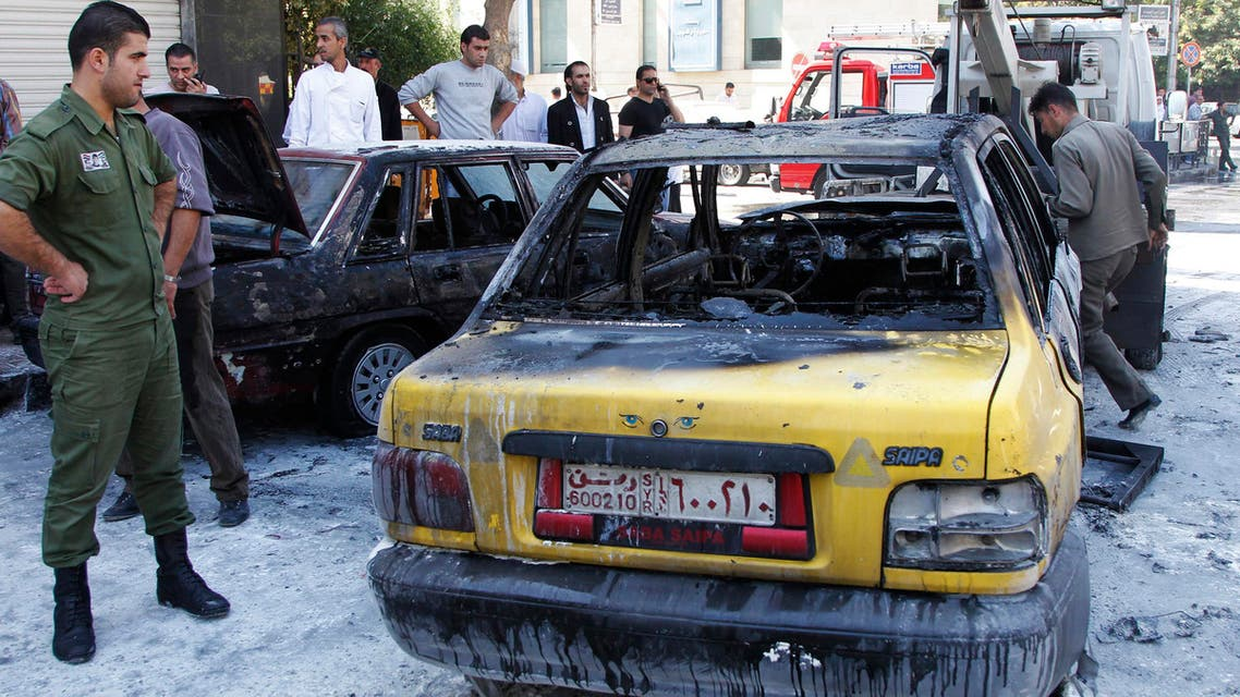 People gather around the wrecked cars after two mortar bombs landed in the al-Nijmah square in Damascus October 12, 2013.