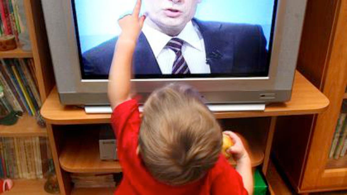 kid touches TV AFP generic