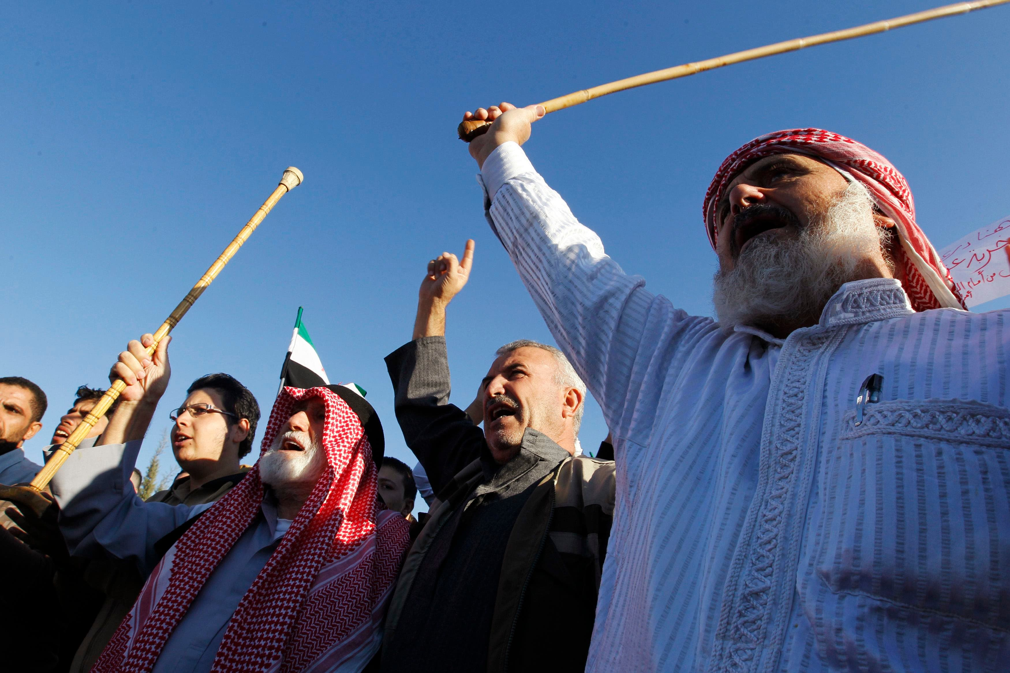 JORDAN: Syrian refugees shout slogans against Syria's President Bashar al-Assad after performing prayers for Eid al-Adha in front of the Syrian embassy in Amman October 15, 2013. (Reuters)