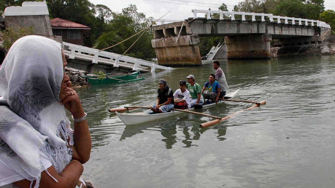 Villagers ride on a boat to cross a river after bridge was damaged in Loon, Bohol, October 16, 2013, a day after an earthquake hit central Philippines.