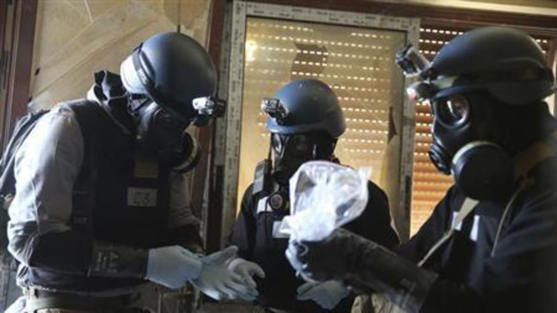 A U.N. chemical weapons expert, wearing a gas mask, holds a plastic bag containing samples from one of the sites of an alleged chemical weapons attack in the Ain Tarma neighborhood of Damascus. (File photo: Reuters)
