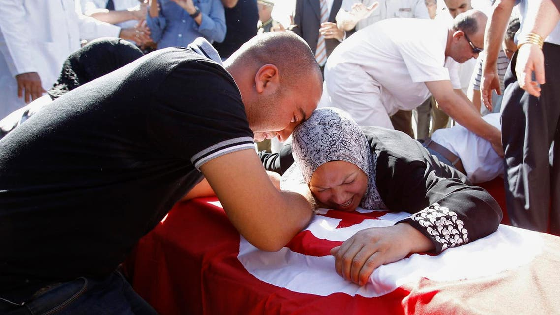 Relatives of one of the Tunisian policemen killed during clashes on Thursday in the northeastern city of Goubellat, mourn during an official memorial ceremony, in Tunis October 18, 2013. reuters