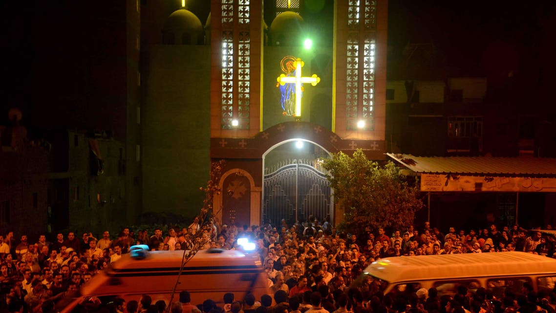 Ambulances drive through the crowd in front of the Virgin Mary Coptic Christian church in Cairo after gunmen on a motorbike shot dead three people late on October 20, 2013, including an eight-year-old girl, in a shooting attack on a group standing outside the church in the Egyptian capital's Al-Warak neighbourhood following a wedding ceremony AFP