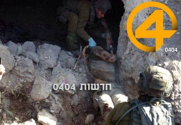 جنود اسرئيليون يخلون جثة الفلسطيني محمد عاصي من المغارة بعد قصفها بالصواريخ