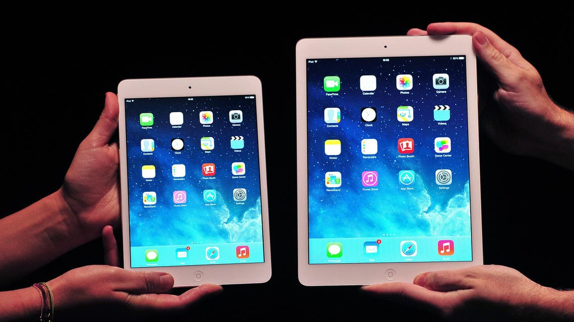 Apple employees show off the new iPad Air (R) and iPad Mini at a satellite launch event in central London on Oct. 22, 2013. (AFP)