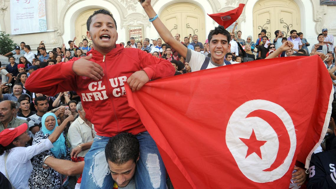 Tunisian young protesters hold a national flag shouting slogans during a demonstration in Tunis' central Habib Bourguiba Avenue on October 23, 2013 demanding the resignation of Tunisia's Islamist-led government, ahead of a national dialogue aimed at ending months of political deadlock.