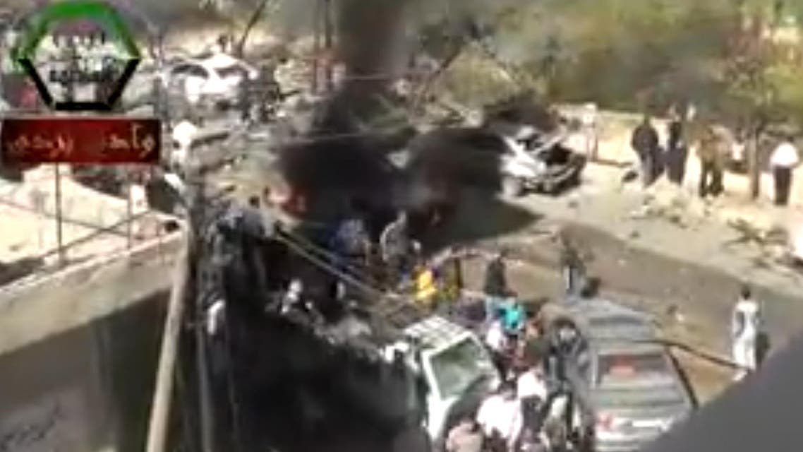 An image grab taken from a video uploaded on October 25, 2013 allegedly shows people gathering on the site of a car bomb attack outside a mosque in the town of Suq Wadi Barada, Damascus. (AFP)