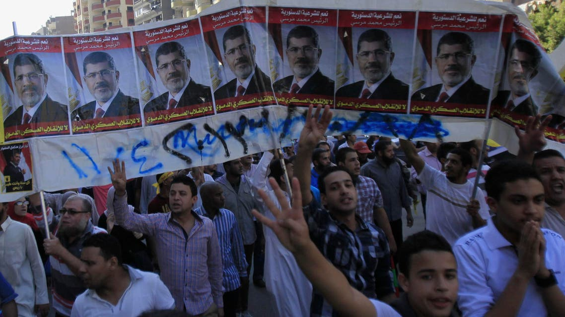 Supporters of the Muslim Brotherhood and ousted Egyptian President Mohammad Mursi shout slogans against the military and interior ministry, under Mursi posters, during a protest near Giza square on October 25, 2013. (Reuters)