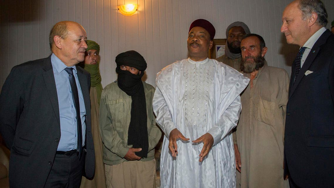 Niger's President Mahamadou Issoufou (C), French Foreign Minister Laurent Fabius (R) and French Defence Minister Jean-Yves Le Drian (L) stand with the four released French hostages in Niamey October 29, 2013.  (Reuters)