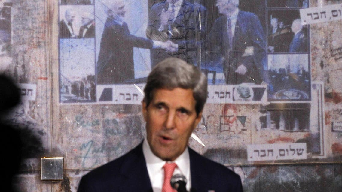 U.S. Secretary of State John Kerry  is pictured in front of a photo showing U.S. President Bill Clinton, Jordan's King Hussein and Yitzhak Rabin, as Kerry marks the 18th anniversary of Rabin's assassination in Tel Aviv, on Nov. 5, 2013. (AFP)