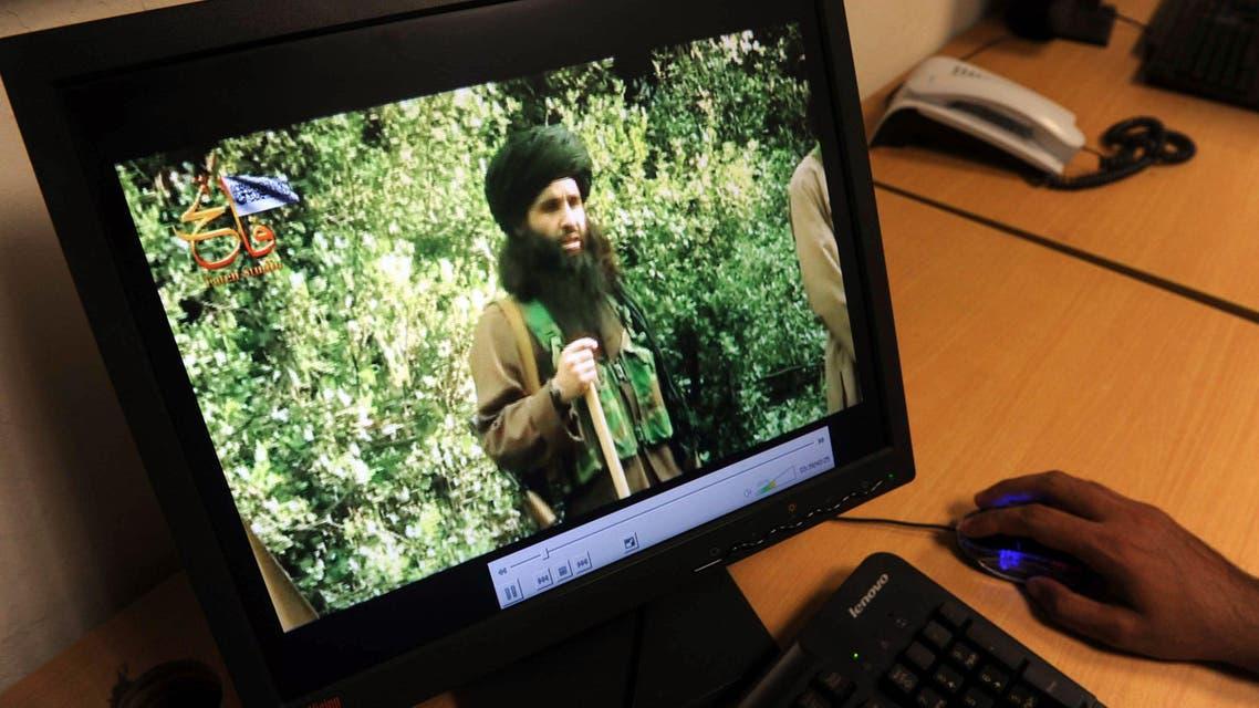 A Pakistani journalist watches a newly released video of radical Pakistani cleric Maulana Fazlullah in Peshawar. (AFP)