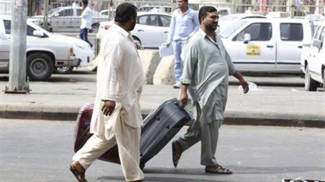 Foreign workers pull their luggage along a street in Riyadh November 4, 2013. reuters