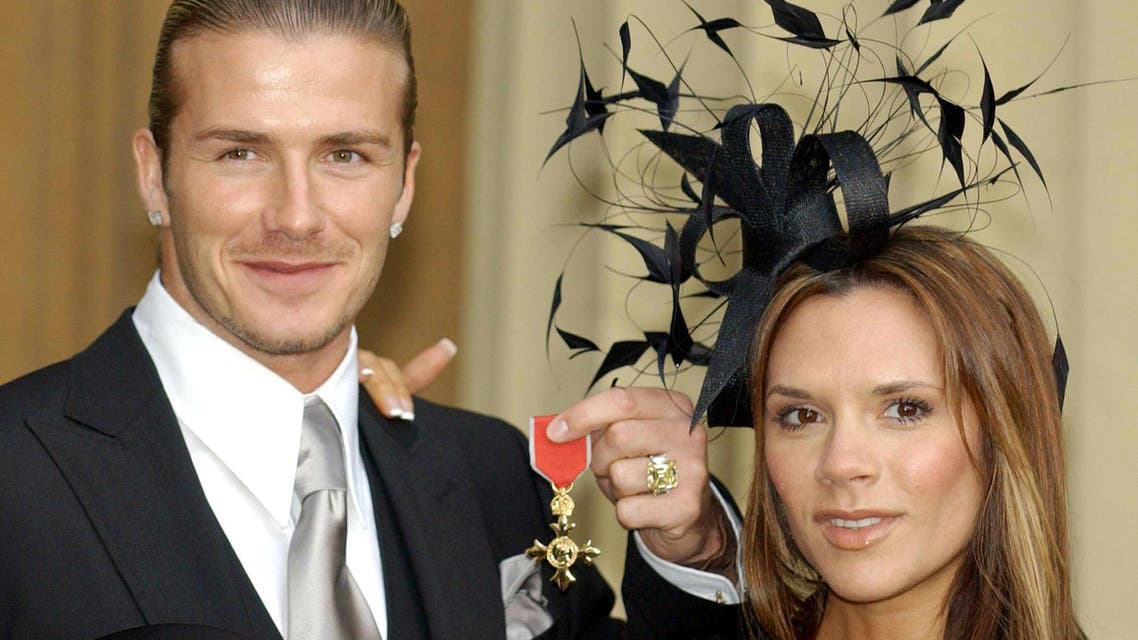 David Beckham, seen with his wife Victoria, collecting his OBE in 2003. (Reuters)