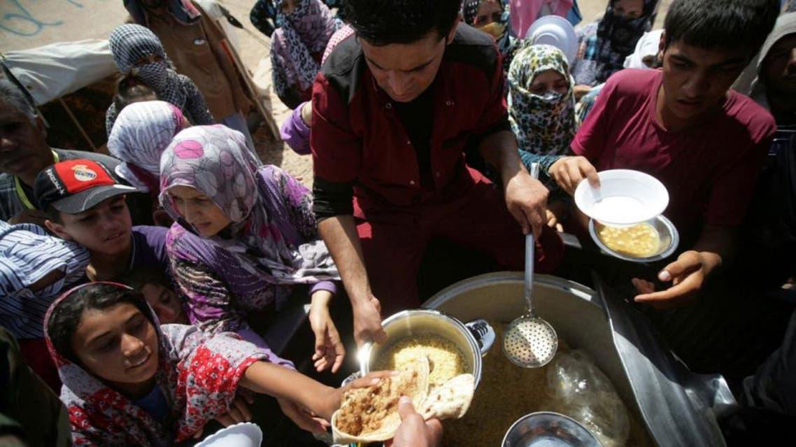 Syrian-Kurdish refugee families queue to get food at the Quru Gusik refugee camp, near Arbil, Iraq afp
