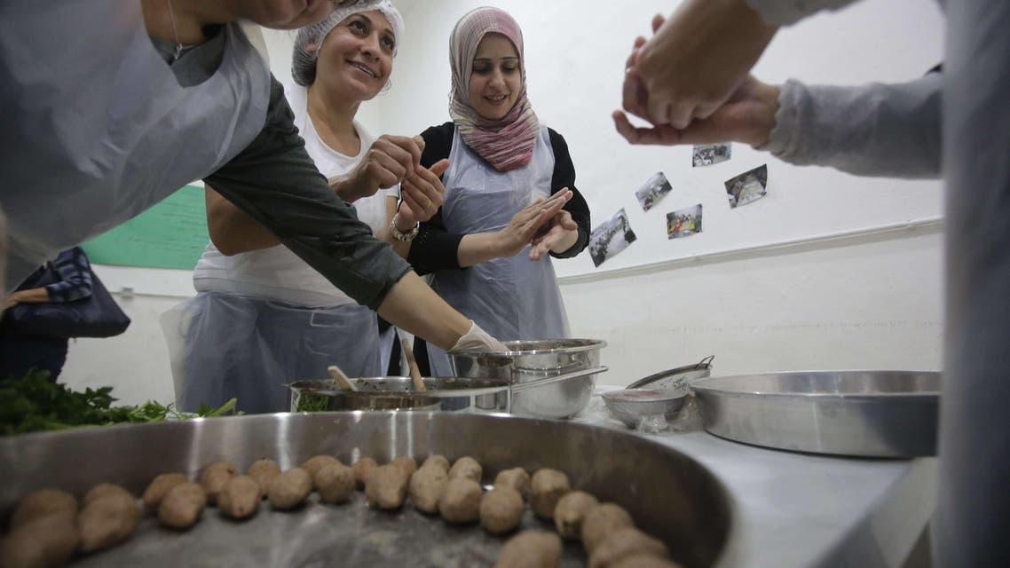 لاجئات سوريات في لبنان يحضرن وجبات