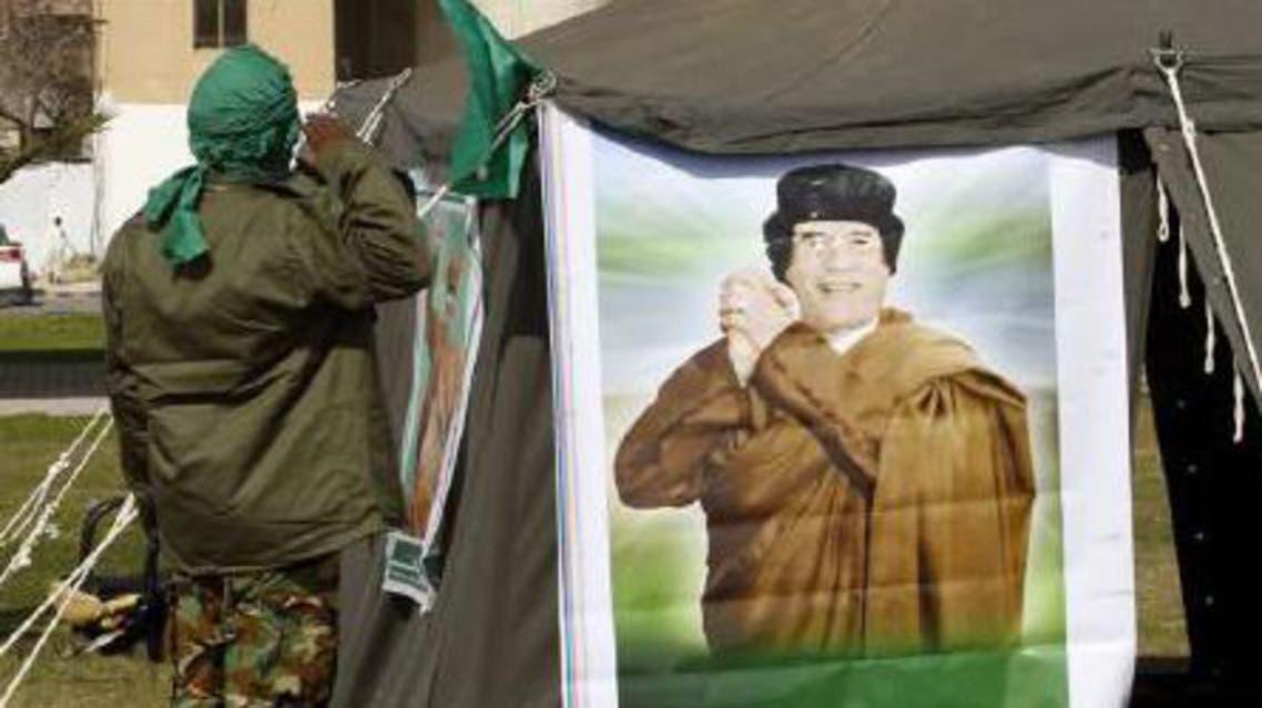 ضابط يؤدي التحية لصورة معمر القذافي في ليبيا