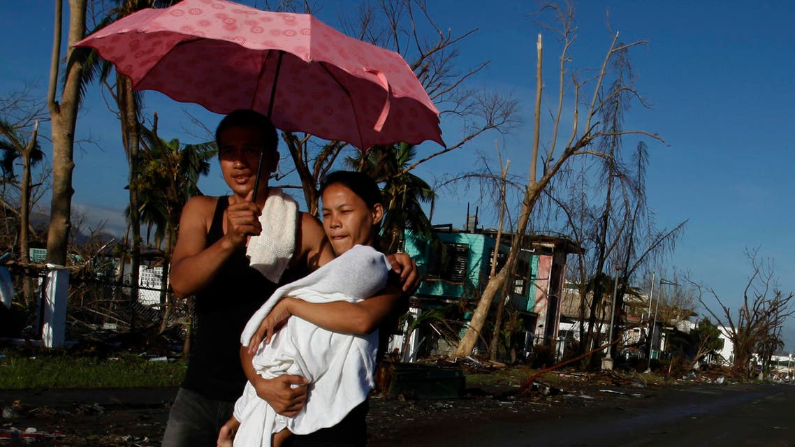 A couple carrying their sick child walk to a Philippine Red Cross service center in Tacloban Nov. 15, 2013. The death toll from a powerful typhoon doubled overnight in one Philippine city alone, reaching 4,000. (Reuters)