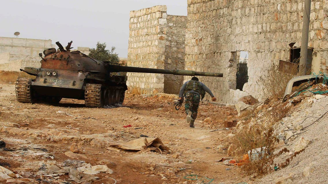 A fighter from Tawhid Brigade runs beside a tank in Base 80 area of Aleppo, November 10, 2013. (Reuters)