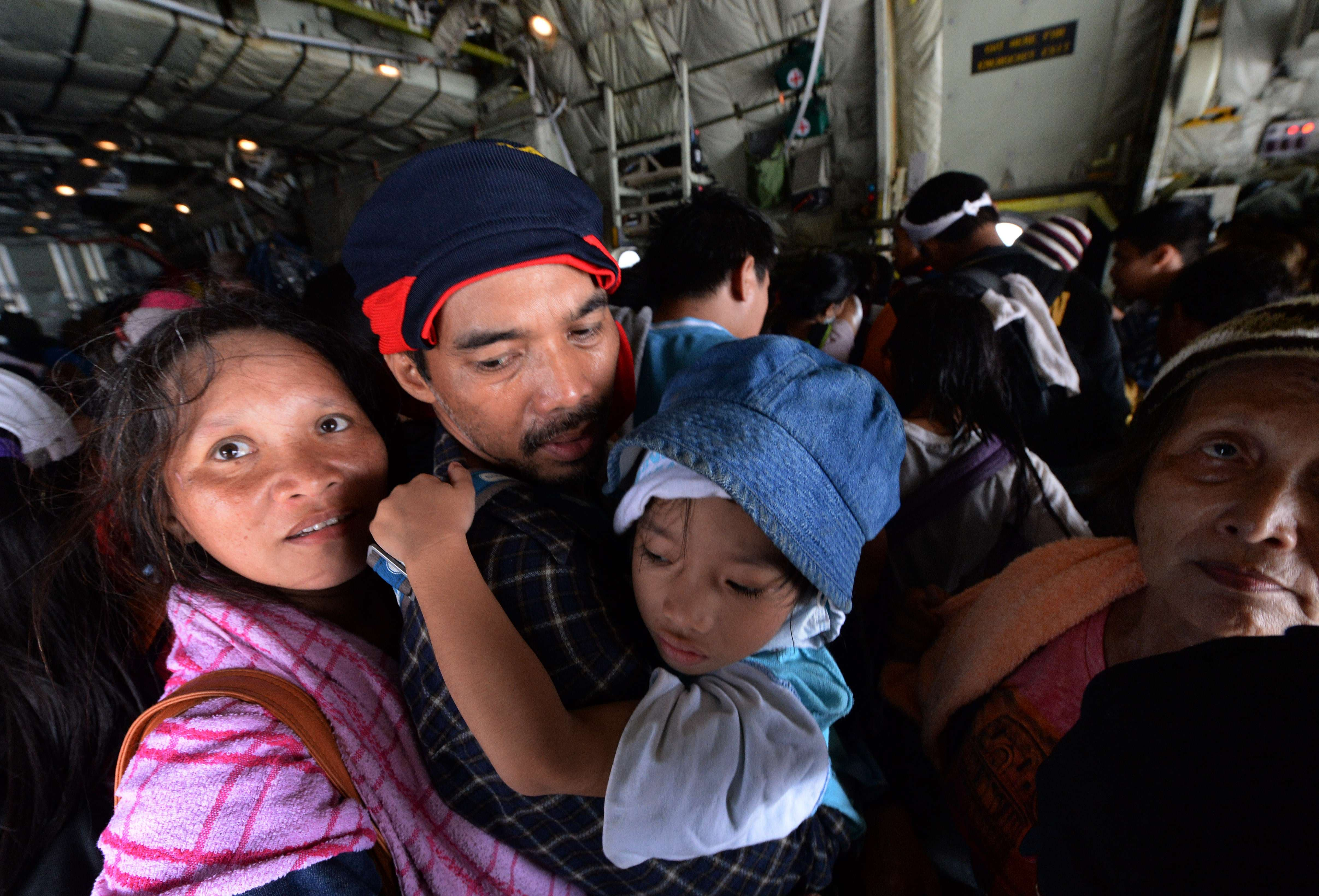 Typhoon survivors board a New Zealand C130 military cargo plane for evacuation at Tacloban airport on Nov. 16, 2013. (AFP)