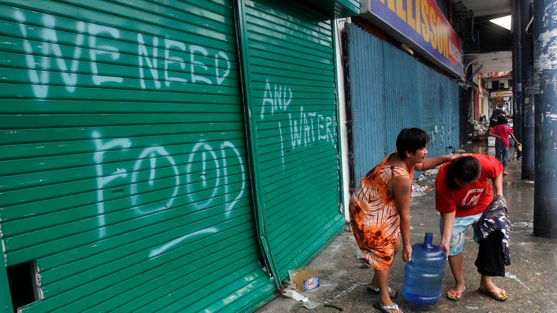 Residents carry a plastic container of drinking water as they walk past a graffiti calling for help after Typhoon Haiyan devastated Tacloban city, central Philippines. (Reuters)